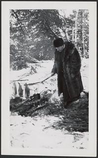 Man tending a kettle and cooking fish over a fire in the snow... / Homme tendant une bouilloire et cuisant du poisson sur un feu dans la neige...