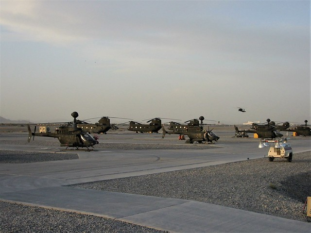 Late afternoon sun on the U.S.Army tarmac at Kandahar Air Base, Afghanistan. At the foreground there are some Bell OH-58D Kiowa Warriors. In the background some CH-47D Chinook and UH-60A Black Hawk helicopters can be seen. Kandahar, Spring 2008.