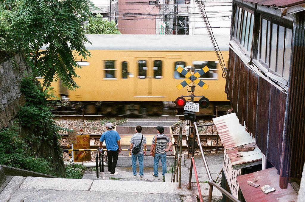 平交道 尾道 おのみち Onomichi, Hiroshima 2015/08/30 後來等到一輛列車經過,畫面中有三個人。以前拍照的時候總是會想要等淨空的畫面,可是這趟出來我想也把當地人都放進去,或是說我不需要再這麼的刻意去營造一個我想要的完美的畫面。  Nikon FM2 / 50mm FUJI X-TRA ISO400 Photo by Toomore