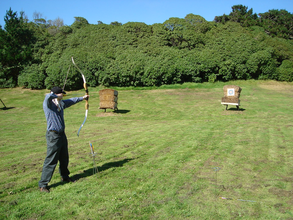 an archer takes aim in the outdoor facility at archery academy