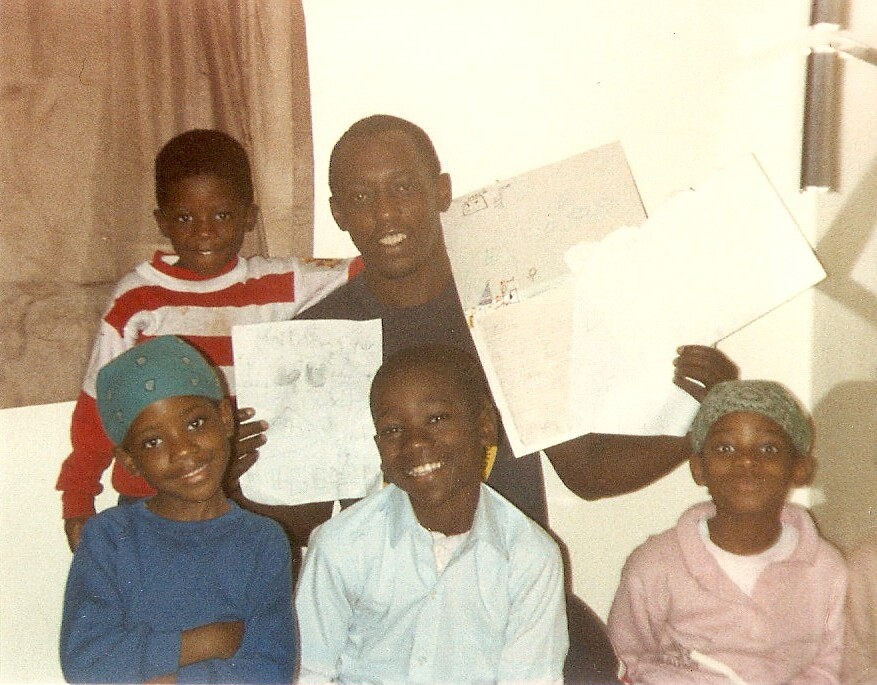 A man surrounded by four children holds up pieces of paper.