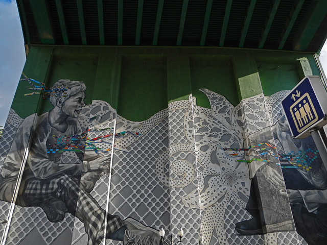 Mural just below the Bilbao Bridge with a sign indicating there's an elevator