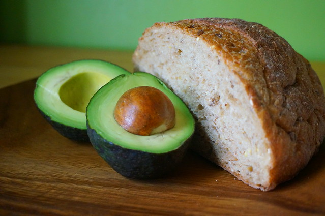 Still life with bread and avocado: two halves of an avocado, one still with pit, lean against the cut edge of a multigrain boule, all in soft lighting