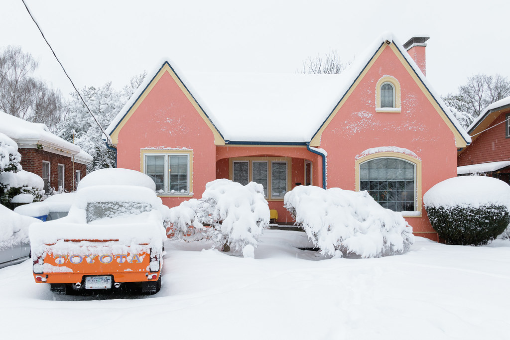 A pink house and an orange truck covered in snow in the Irvington neighborhood of Portland, Oregon