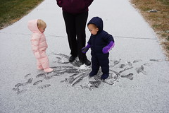 The twins make prints in the snow on the driveway