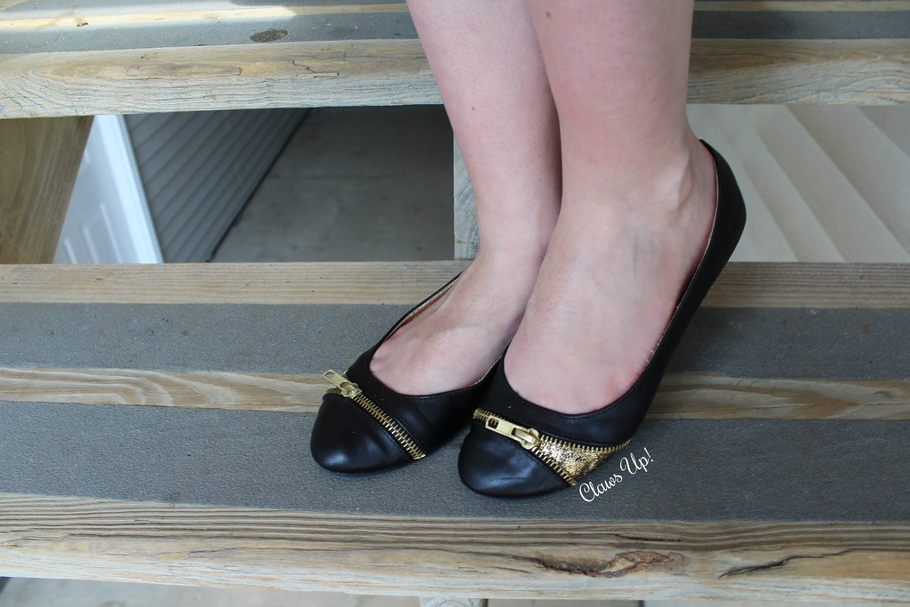 Black flats with gold and zipper embellishments.