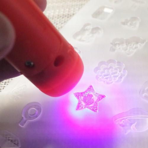 型にペンのピグメントを入れて、UVライトで硬化中。