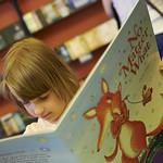 Enjoying a book in the Baillie Gifford Children's Bookshop | Little girl enjoys one of Debi Gliori's books in the Children's Bookshop © Helen Jones
