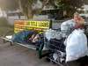 Homeless man sleeping on a street bench at sunrise by Gilbert Mercier