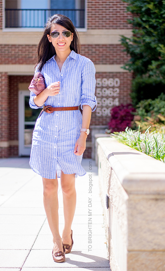 blue and pink striped shirtdress, brown belt, pink metallic clutch, oversized watch, brown loafers