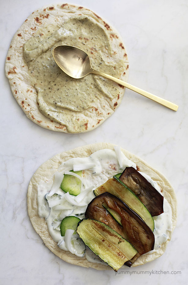 Making vegetarian and vegan gyros with tzatziki, hummus, flatbread, grilled eggplant and zucchini, and cucumber.