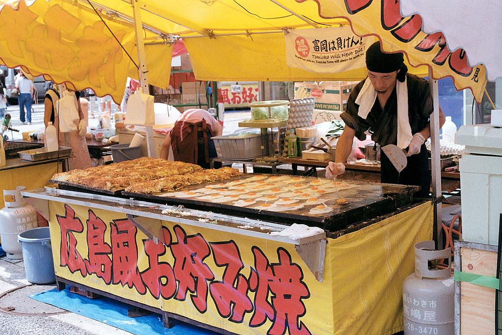 """七夕祭 Iwaki (いわき市 Iwaki-shi), Fukushima 2015/08/06 一大鍋的廣島燒,雖然我不是很清楚和大阪燒的差異。正在一大鍋上面打很多蛋 ...  Nikon FM2 / 50mm Kodak ColorPlus ISO200  <a href=""""http://blog.toomore.net/2015/08/blog-post.html"""" rel=""""noreferrer nofollow"""">blog.toomore.net/2015/08/blog-post.html</a> Photo by Toomore"""