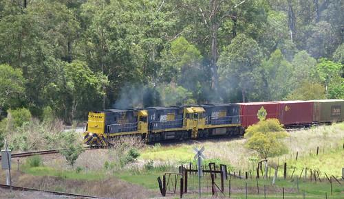 Running long end leading due to an earlier loco failure, NR27+NR69+NR44 bring train 6BA6 through Mount George, NSW. (1)