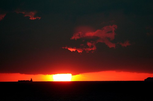 dramatic sunset as ship sails by