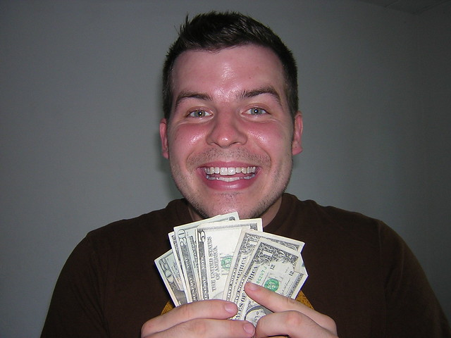 Happy with money in Vegas by flickr user greggoconnell