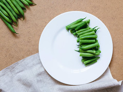Sliced green beans on a white plate and a bunch of…