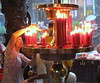 Temple worker tends to the candle offerings by scooping away melted wax, Longshan Temple, Taipei, 2015