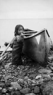Inuit child with a canoe / Enfant inuit à côté d'un canot