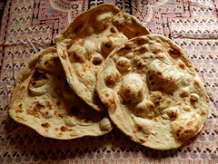 Three thin round flatbreads with large blisters from the cooking process.  They are lying on a patterned tablecloth.