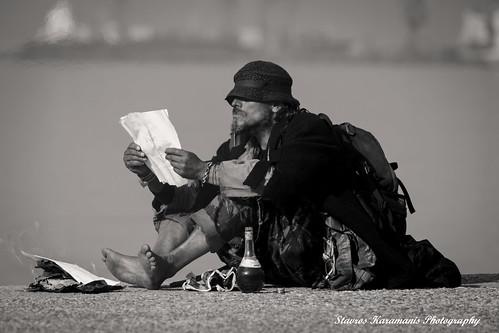 A homeless man warms his feet