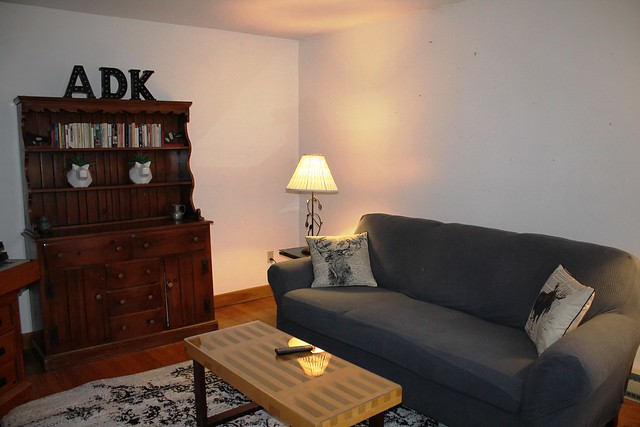 Living area with hardwood floors, ample light overlooking the woods; Flat screen TV; Newly furnished with over sized sofa and coffee table;