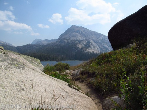 The trail squeezes between a rock and the hillside as it traverses the Big Sandy Lake Shoreline, Wind River Range, Wyoming
