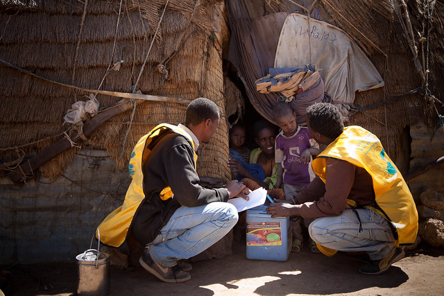 Salah Kedir, clinical nurse (left), fills out vaccination records outside the hut of Sophia Abdi in Dudejirma sub-district, Rer Hassen Settlement,Tulugulid District, Fafan Zone. Three year old Sehardid Ali Hassen (standing) and his baby brother Umer Keyir Ali Hassen, one years old, have been vaccinatied by clinical nurse Ermias Amare (right), during the Polio NIDs campaign in Somali Region, 9 February 2015. THe half-tick mark on the hut's opening flap indicates that not all the children who live their under the age of five have been vaccinated.Sophia's eldest daughter (five years old) is out wtending the families goats, and the vaccination team makes an appointment to return the next day to vaccinate her as well. ©UNICEF Ethiopia/2015/Getachew