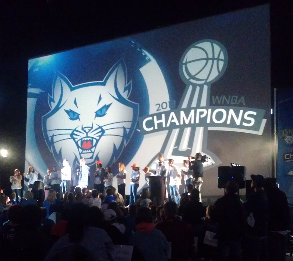 The team on stage in front of a big 2013 WNBA Champions banner