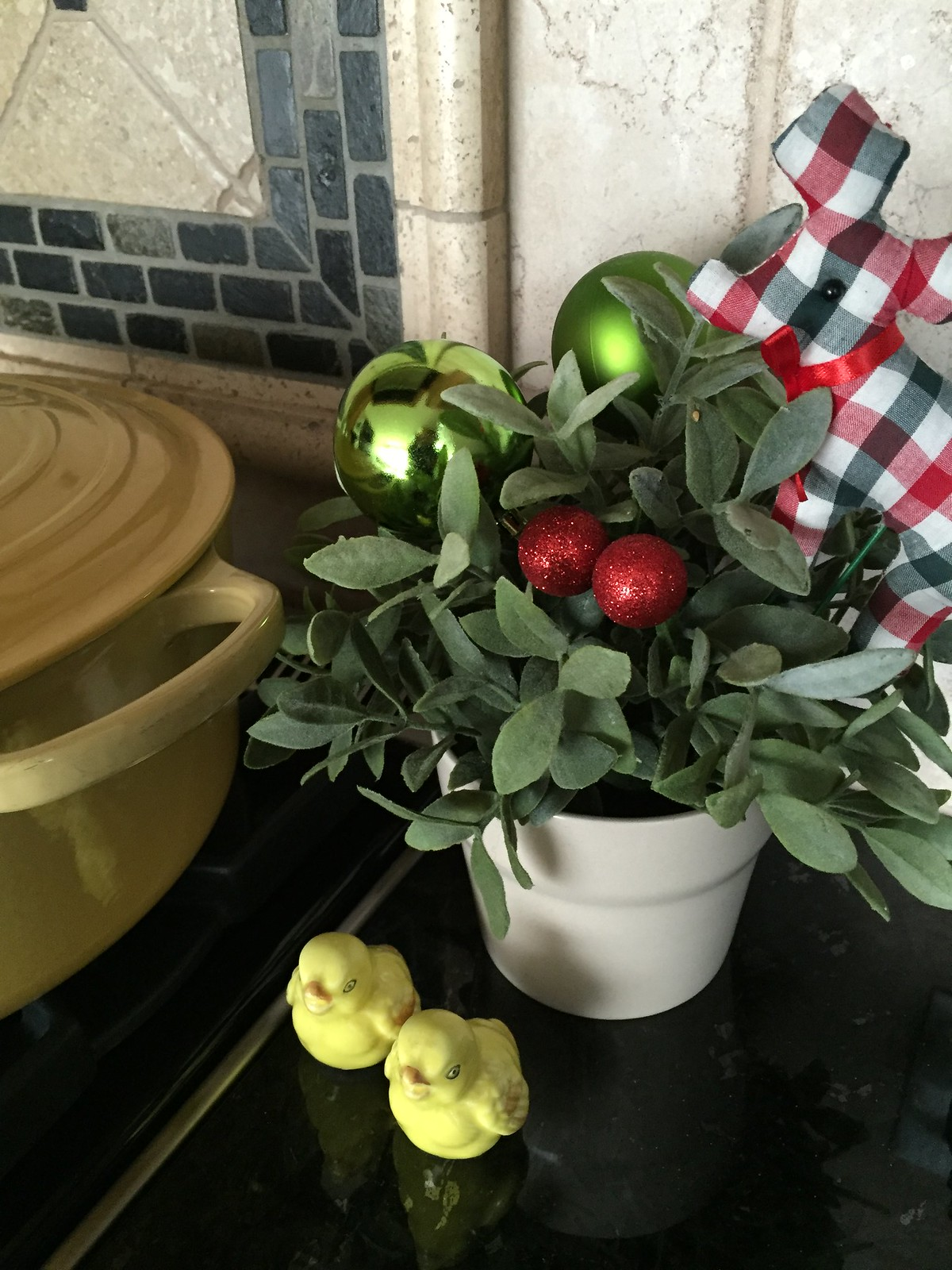 small christmas pot with green baubles on stove beside yellow pot