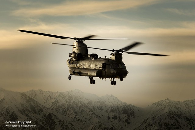 An RAF Chinook helicopter in silhouette, flying over Afghanistan.