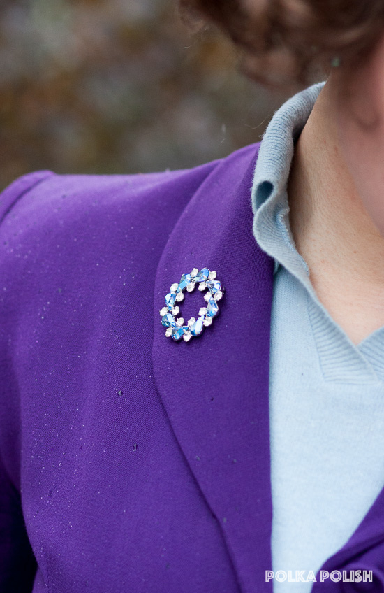 Ice blue AB crystal B. David costume brooch on the lapel of a purple 1940s jacket
