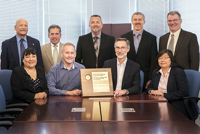 The DOE Secretary's Achievement Award is presented to the RLUOB Transfer Team. Top (from left): David Gallimore, Brett Cederdahl, Mike Parkes, Tim Leckbee and Tim Nelson. Bottom (from left): Denise Thronas, acting Deputy Laboratory Director Paul Henry, Laboratory Director Charles McMillan and Amy Wong.