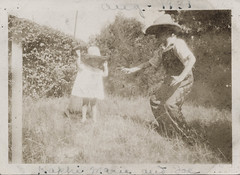 Little boy points a toy pistol at a young cowboy