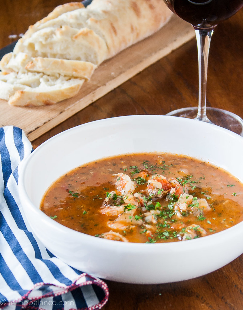 tomato based seafood stew with shrimp with a loaf of bread and glass of wine