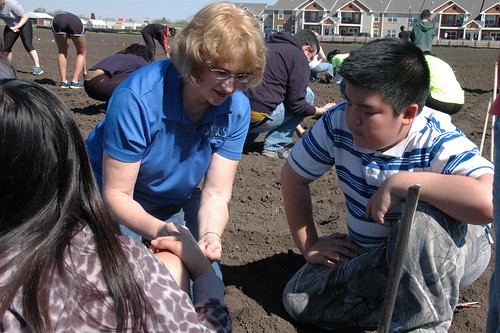 NRCS District Conservationist Larette Kolbe helps Storm Lake student volunteers plant rows of vegetables.