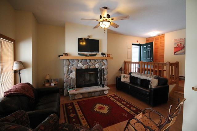 Lakeside 9 living area with stone fireplace and open views of the lake and mountains;
