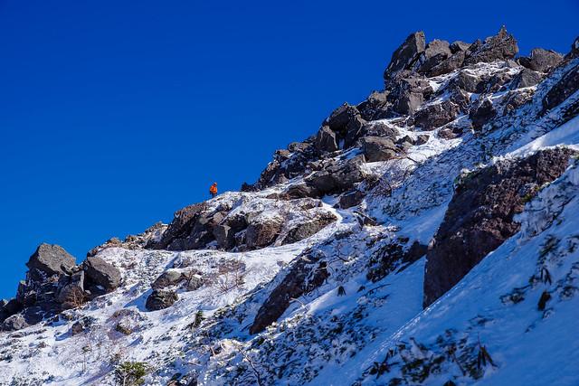 東天狗岳直下の岩場を登る登山者