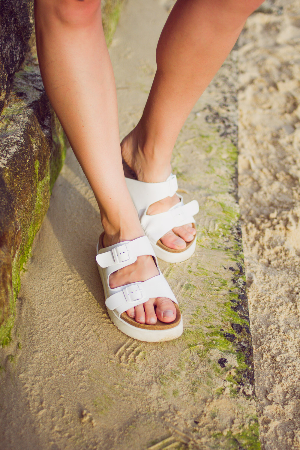 white leather birkenstocks on the beach