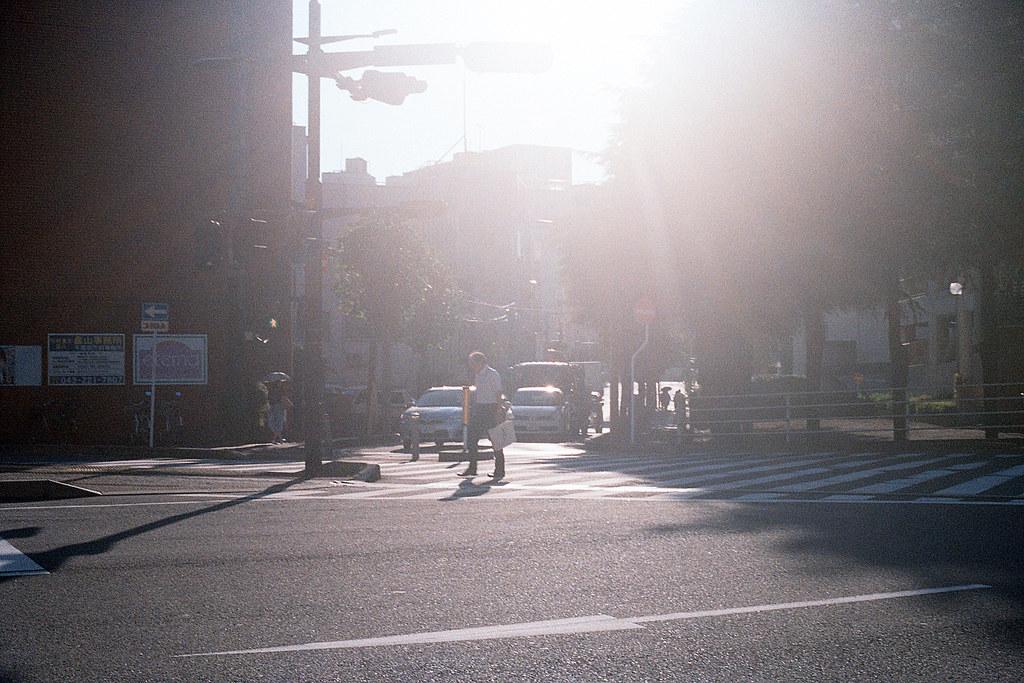 """千葉県庁前 Chiba Kenchomae 2015/08/05 在千葉県庁前拍攝的,那時候大逆光,又看到一個老人過馬路,就趕快把這畫面拍下來。  Nikon FM2 / 50mm Kodak ColorPlus ISO200  <a href=""""http://blog.toomore.net/2015/08/blog-post.html"""" rel=""""noreferrer nofollow"""">blog.toomore.net/2015/08/blog-post.html</a> Photo by Toomore"""