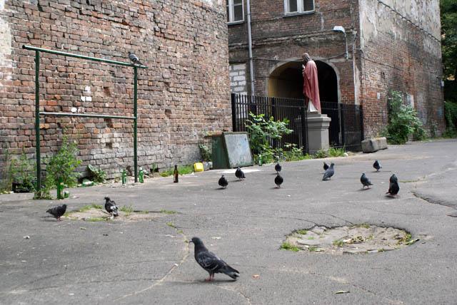 Cour et batiment en brique, statue et pigeons avec une structure en metal pour taper les tapis