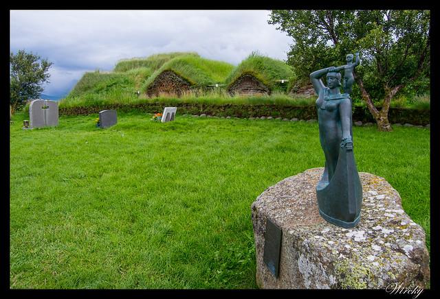 Escultura de la primera madre europea en América junto a granja de césped Glaumbaer