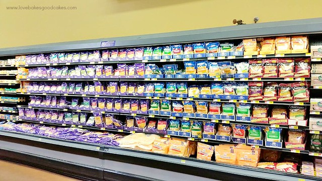 A grocery store isle of the cold section with products on the shelves.