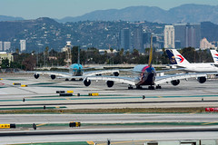 A pair of Airbus A380s taxi at LAX