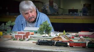 Jim Kalenowski looks on as John Wallis' Christmas train passes through Joe Peacock's set of Wood Yard themed T-TRAK Modules at the TCA Raleigh Show