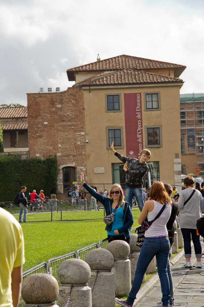 People in pose holding up Leaning Tower of Pisa