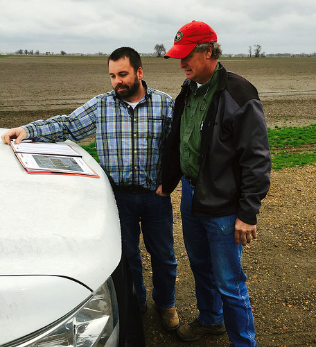 Two men looking at plans on a truck in front of farmland