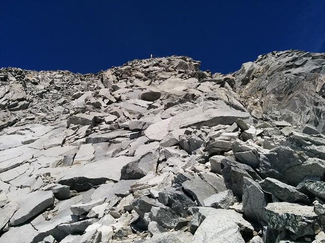Gipfelkreuz in Sicht, über Blockwerk und lose Steine geht es das letzte Stück empor