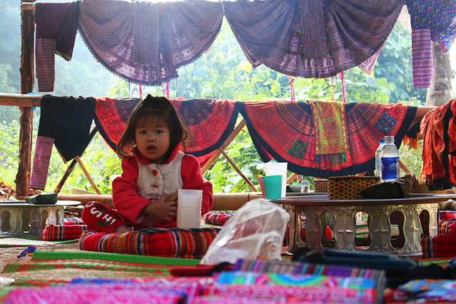 A local girl sitting in a beautifully decorated hut