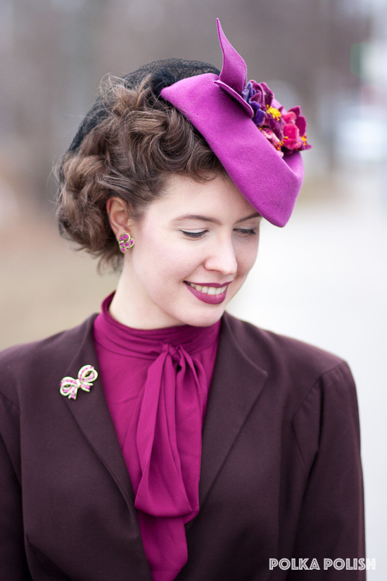 1940s tilt hat in pink topped with a cluster of velvet flowers, paired with a brown suit and raspberry pussy-bow blouse