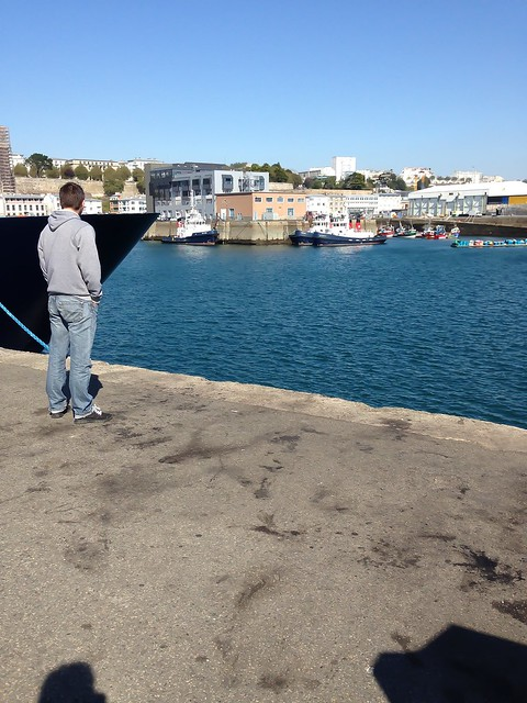 A man in front of a boat in Brest, France.